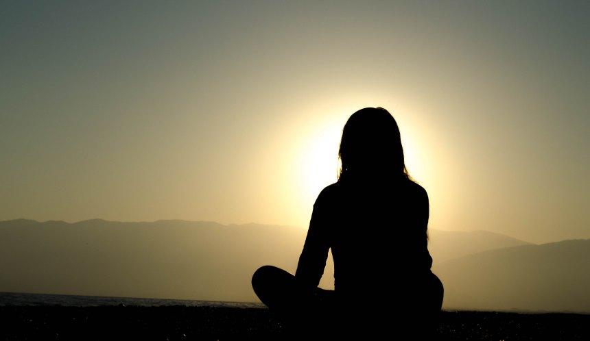 Femme assise face au soleil